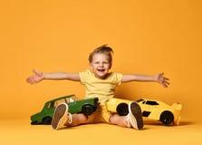 黄色T恤杉的孩子坐与大跑车玩具的男孩和短裤当生日礼物用被举的手  库存照片