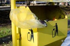 黄色trashcan与标志和垃圾 免版税图库摄影