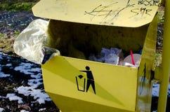 黄色trashcan与标志和垃圾 库存照片
