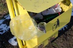 黄色trashcan与标志和垃圾 免版税库存照片