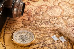 黄铜指南针、一支木铅笔和一台老照相机在一张老葡萄酒地图说谎 免版税库存图片