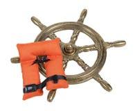 黄铜船轮子和救生背心 免版税库存照片