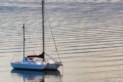 黎明光反射小船和起波纹的水 库存图片