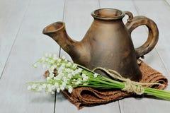 黏土棕色茶壶与铃兰花束的异常的专属形状栓与在粗砺的浅褐色的黄麻餐巾的麻线 免版税图库摄影