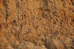 黏土红色沙子墙壁纹理与许多的另外深度镇压  库存照片