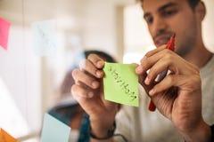 黏贴关于玻璃墙的商人稠粘的笔记在办公室 库存图片