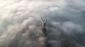 黏附在他们外面的秋天雾和祖国纪念碑厚实的云彩  库存图片