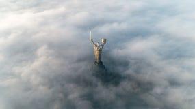 黏附在他们外面的秋天雾和祖国纪念碑厚实的云彩  免版税库存照片