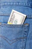黏附在外面的盒美元牛仔裤装在口袋里 库存照片