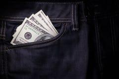 黏附在深蓝牛仔裤外面的美国美元装在口袋里 免版税库存照片