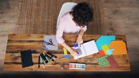 黏附在笔记本的繁忙的女性设计师顶视图纸图使用在家运转的胶浆棍子单独 创造性 股票录像