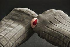 黏附在袜子的孔外面的脚趾 免版税库存照片