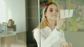 黏附稠粘的笔记的年轻女实业家在玻璃在办公室 股票录像