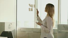 黏附稠粘的笔记的年轻女实业家在玻璃在办公室 影视素材