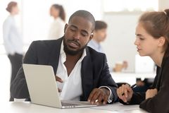 黑人与看膝上型计算机的客户的经纪承保人咨询的工作 库存照片