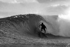 黑人冲浪者冲浪的管白色 免版税库存图片