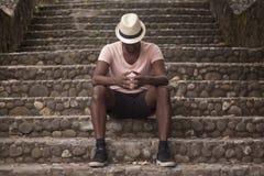 黑人坐一个老镇的楼梯 免版税库存图片
