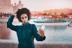 黑人女孩在做selfie的河附近的莫斯科 免版税库存图片