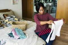 黑人妇女折叠的衣裳在卧室 免版税图库摄影