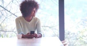 黑人妇女饮用的咖啡和在家使用一个手机 免版税库存图片