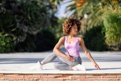 黑人妇女,非洲的发型,做在散步的瑜伽 库存照片