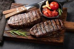 黑人安格斯特写镜头立即可食的牛排上面刀片牛肉品种用格栅蕃茄,大蒜和一个木板的 完成的盘 免版税库存图片