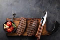 黑人安格斯特写镜头立即可食的牛排上面刀片牛肉品种用格栅蕃茄,大蒜和一个木板的 完成的盘 免版税库存照片