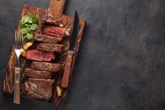 黑人安格斯特写镜头立即可食的牛排纽约牛肉品种用草本、大蒜和黄油在一个木板 完成的盘 免版税库存图片