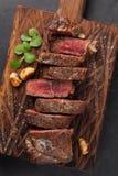 黑人安格斯特写镜头立即可食的牛排纽约牛肉品种用草本、大蒜和黄油在一个木板 完成的盘 库存照片