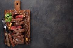 黑人安格斯特写镜头立即可食的牛排纽约牛肉品种用草本、大蒜和黄油在一个木板 完成的盘 免版税库存照片