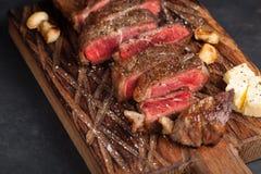 黑人安格斯特写镜头立即可食的牛排纽约牛肉品种用草本、大蒜和黄油在一个木板 完成的盘 免版税图库摄影