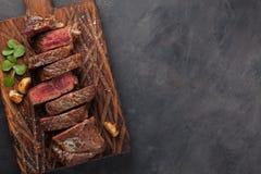 黑人安格斯特写镜头立即可食的牛排纽约牛肉品种用草本、大蒜和黄油在一个木板 的treadled 免版税库存图片