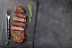 黑人安格斯特写镜头立即可食的牛排纽约牛肉品种用草本、大蒜和黄油在一个石委员会 完成的盘f 免版税图库摄影