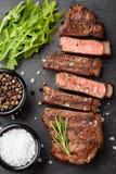 黑人安格斯特写镜头立即可食的牛排纽约牛肉品种用草本、大蒜和黄油在一个石委员会 的treadled 免版税库存照片