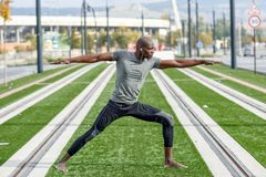 黑人实践的瑜伽在都市背景中 免版税库存图片