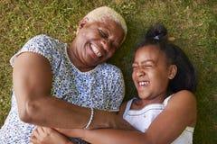 黑人说谎在草,顶上的关闭的女孩和祖母  库存图片