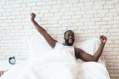 黑人,被唤醒的人在床上延长  免版税库存图片