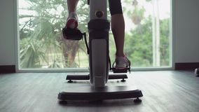 黑体育穿戴的女孩在锻炼脚踏车,后面看法有力地工作 股票视频