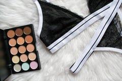 黑体育设置了在一张白色毛皮的鞋带女用贴身内衣裤 手表, eyeshado 免版税库存照片