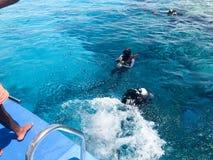 黑佩戴水肺的潜水衣服、一个男人和一名妇女的两个潜水者有氧气瓶的沉没在透明大海下于海, Th 免版税库存照片
