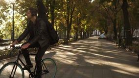 黑便服的,骑自行车的耳机愉快,微笑的年轻人由有吉他的被铺的城市公园在黑色 影视素材