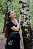 黑俄国礼服的微笑的俏丽的女孩有刺绣的倾斜了反对桦树 免版税图库摄影