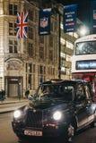 黑出租汽车和公共汽车在摄政的街道,伦敦上,在美国橄榄球联盟旗子下,在晚上 图库摄影