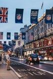黑出租汽车和红色公共汽车在摄政的街道,伦敦,英国上 库存照片