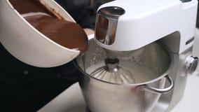 黑制服的妇女糖果商奶油为巧克力沫丝淋蛋糕做准备 烹调奶油甜点蛋糕的阶段 股票录像