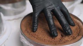 黑制服的妇女糖果商奶油为巧克力沫丝淋蛋糕做准备 烹调奶油甜点蛋糕的阶段 影视素材
