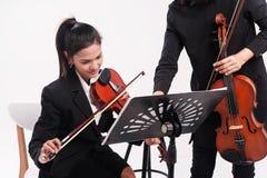 黑制服的秀丽夫人由小提琴老师学习小提琴,在演播室音乐室 库存照片
