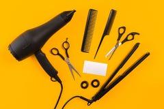 黑发烘干机、梳子和剪刀在黄色纸背景 顶视图 库存图片
