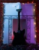 黑吉他在一只白色长袜反对壁炉 免版税图库摄影