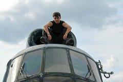 黑和未玷污的一个年轻人在军事起动坐直升机的屋顶 免版税库存图片